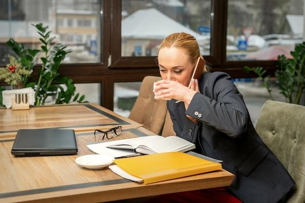 Drukke jonge zakenvrouw koffie drinken praten over de smartphone op het werk in een café