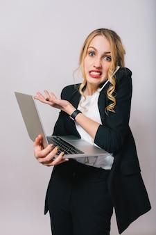 Drukke kantoor werktijd van verbaasde grappige jonge blonde vrouw in wit overhemd en zwarte jas op zoek geïsoleerd. praten aan de telefoon, werken met laptop, werknemer, baan, manager