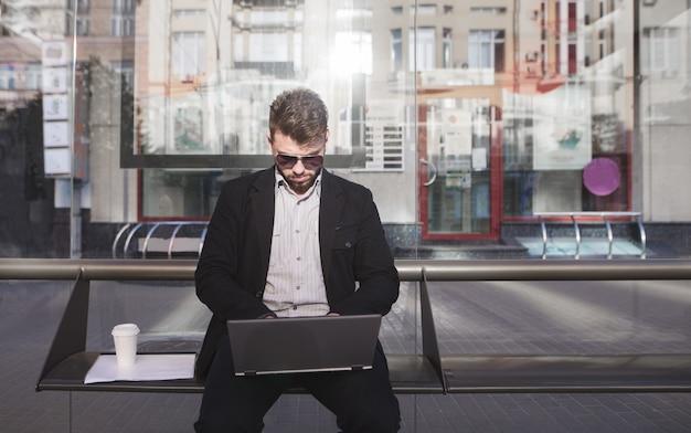Drukke kantoormedewerker zit bij een bushalte en werkt op een laptop.