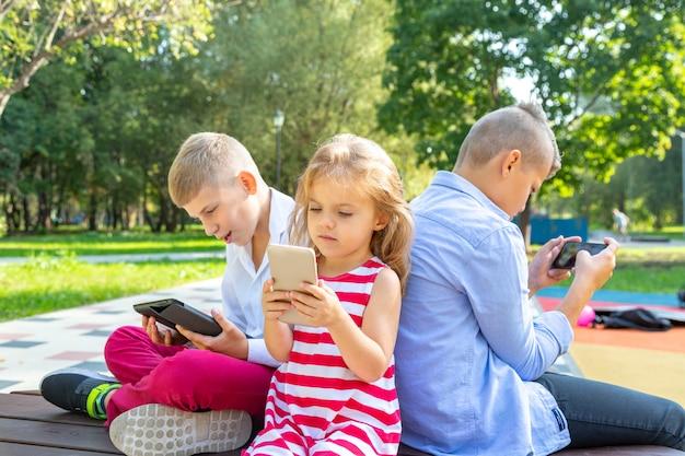 Drukke kinderen kijken naar hun telefoons sms'en en spelen buiten zitten