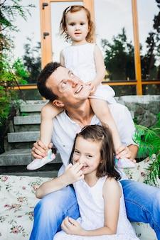 Drukke kleine meisjes zitten met hun vader in voetstappen