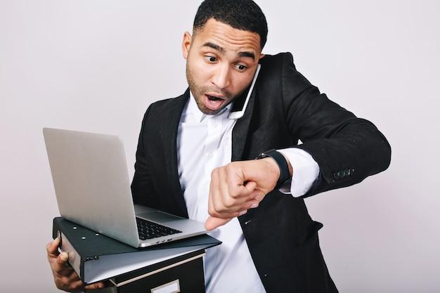 Drukke knappe jongen in wit overhemd en zwarte jas praten aan de telefoon, mappen, laptop vasthouden, kijkt verbaasd op horloge. te laat zijn, vergadering, kantoormedewerker, carrière.
