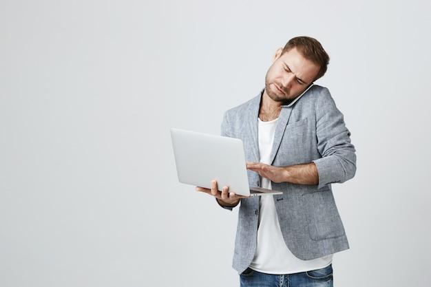 Drukke knappe zakenman die op telefoon spreekt en laptop met behulp van
