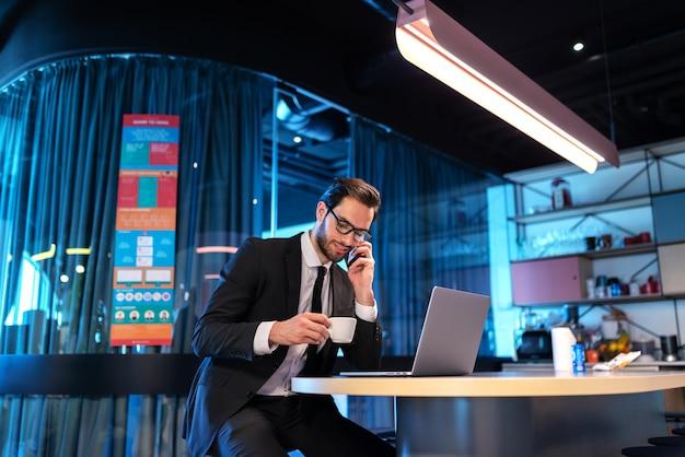 Drukke lachende succesvolle advocaat zit aan de balie en drinkt koffie terwijl hij met zijn cliënt praat.