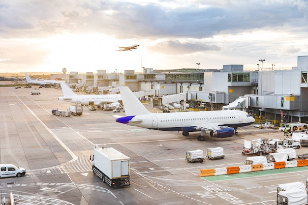 Drukke luchthavenmening met vliegtuigen en de dienstvoertuigen bij zonsondergang