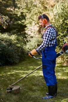 Drukke man die een weedwacker gebruikt in de tuin