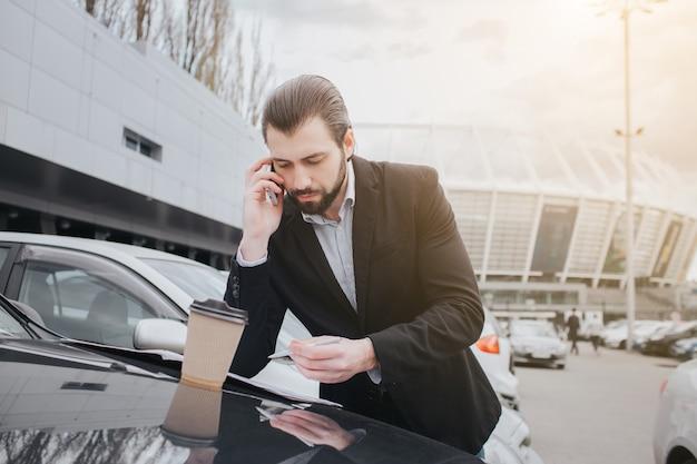 Drukke man heeft haast, hij heeft geen tijd, hij gaat onderweg telefoneren. zakenman doet meerdere taken verkoop van auto's, de koper of verkoper is het invullen van lege formulieren op de auto.