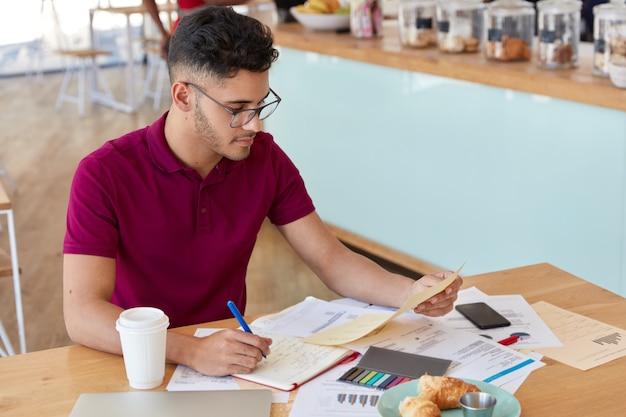 Drukke mannelijke expert bestudeert marketingkwesties, omringd door documenten, leert grafieken en diagrammen, gebruikt stickes en notitieblok om informatie op te schrijven, brengt lunchtijd door in cafetaria of koffiebar