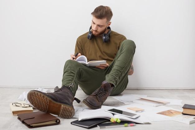 Drukke mannelijke student draagt vrijetijdskleding en laarzen, schrijft aantekeningen en is betrokken bij het studeren voor de sessie