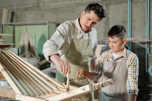 Drukke middelbare leeftijd vader in schort en zijn tienerzoon vernis aanbrengen op hout tijdens het maken van houten stoel in timmerwerkplaats