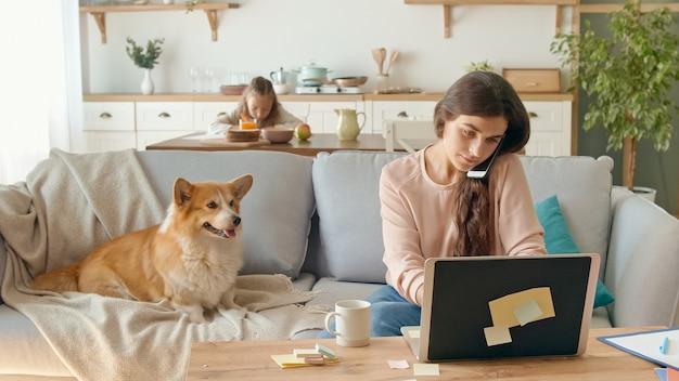 Drukke moeder die op afstand probeert te werken vanuit huis. op de achtergrond zit haar dochter aan een bureau, terwijl haar moeder met een laptop aan het werk is en een zakelijk gesprek voert aan de telefoon.