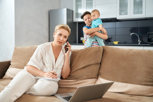 Drukke moeder die thuis werkt terwijl haar zoons dichtbij spelen