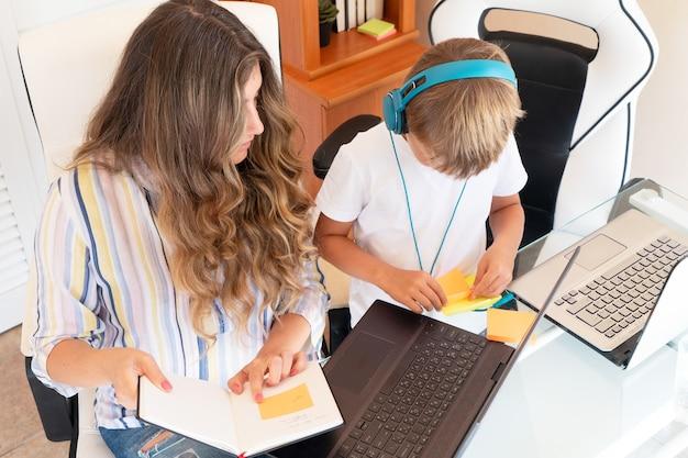 Drukke moeder met zijn zoonskind tijdens quarantaine. blijf thuis concept. online werken en leren tegelijk tijdens quarantaine. werkende ouders met kinderen.