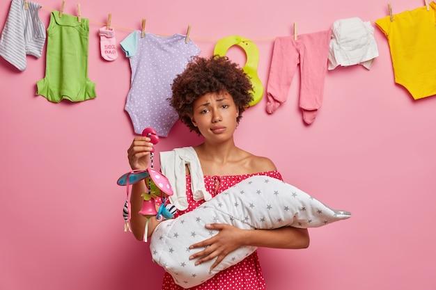 Drukke moeder verzorgt de baby, heeft slapeloze nachten, omhelst de baby gewikkeld in een deken, houdt mobiel vast, uitgeput na het wassen van kinderkleren, wil een dutje doen. moederschap concept