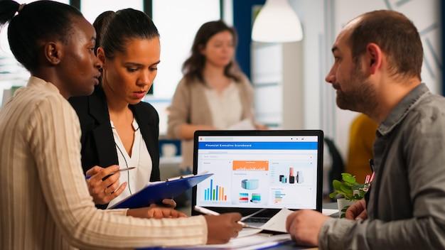 Drukke multiculturele, diverse werknemers die jaarlijkse financiële statistieken analyseren, zittend aan een bureau voor een laptop met documenten die op zoek zijn naar zakelijke oplossingen. team van zakenmensen die in bedrijf werken