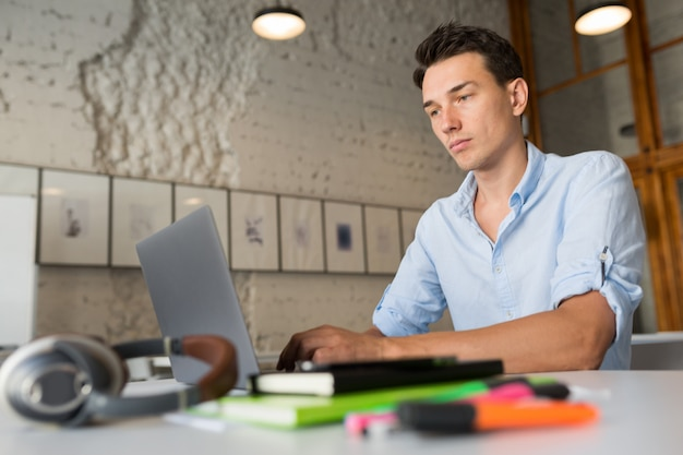 Drukke online externe werknemer jonge zelfverzekerde man aan het werk op laptop