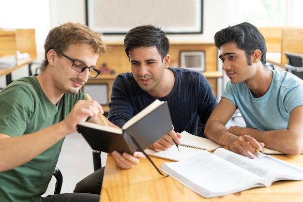 Drukke peinzende multi-etnische studenten die voor examen voorbereidingen treffen
