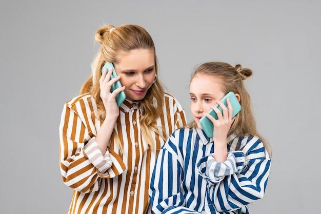 Drukke positieve meid van verschillende leeftijden die op mobiele telefoons praat en dagelijks nieuws bespreekt