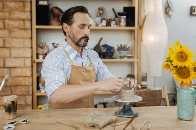 Drukke pottenbakker. donkerharige bebaarde pottenbakker die aan de houten tafel zit en bezig is met het werken met pottenbakkersschijf