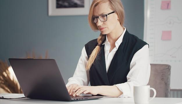 Drukke rijpe blonde zakenvrouw bezig met laptop zittend aan een bureau met whiteboard op achtergrond