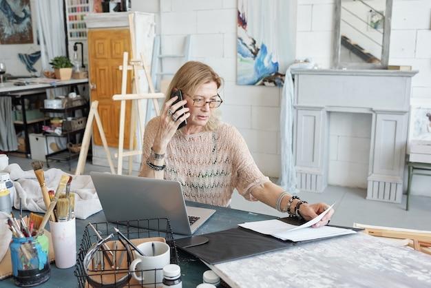 Drukke rijpe vrouw in brillen zit aan bureau en de behandeling van papieren tijdens het gesprek met de klant via de telefoon in de kunststudio