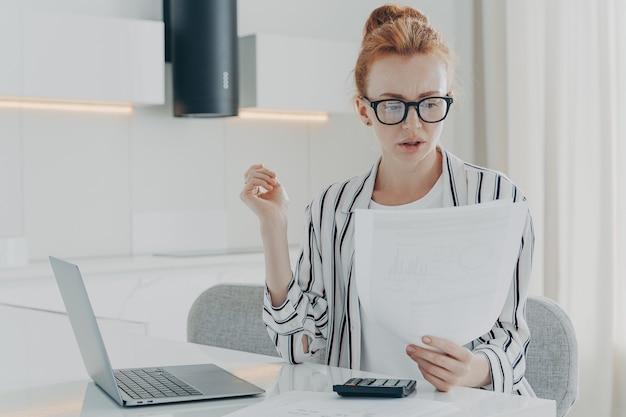 Drukke roodharige vrouw financier maakt zakelijke financiële boekhouding berekent iets