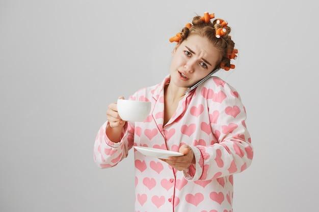 Drukke schattig meisje in haarkrulspelden en pyjama's, koffie drinken en praten over de telefoon
