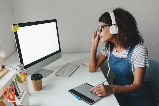 Drukke schattig meisje in vintage outfit met behulp van tablet voor werk tijd doorbrengen op kantoor