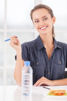 Drukke schoonheid. mooie jonge vrouw die pen in haar hand houdt en glimlacht terwijl sandwich en een fles water op tafel liggen