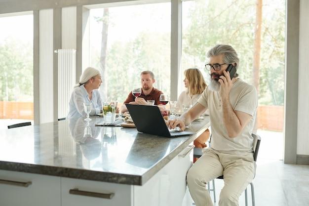 Drukke senior bebaarde vader in bril met behulp van laptop en praten via de telefoon tijdens het werken tijdens het familiediner