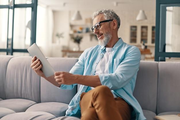 Drukke senior man in casual kleding met behulp van digitale tablet terwijl hij thuis op de bank zit