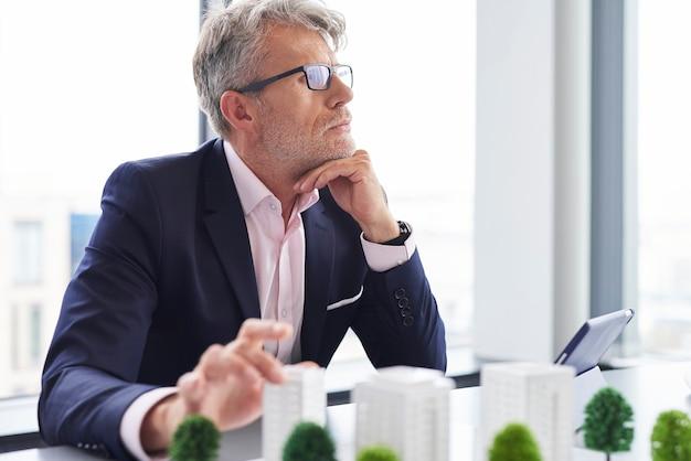 Drukke senior zakenman die nadenkt over nieuwe oplossingen