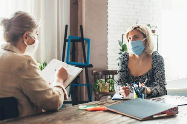 Drukke senior zakenvrouw werken vanuit huis met een cliënt die een medisch masker draagt