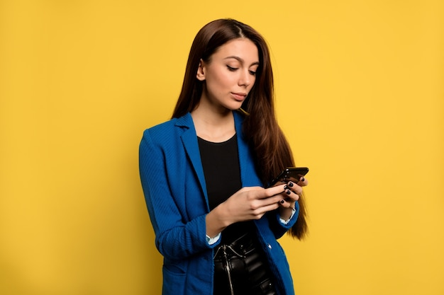 Drukke stijlvolle zakenvrouw met lang donker haar met behulp van smartphone over geïsoleerde muur. europese vrouw scrollende telefoon over gele muur