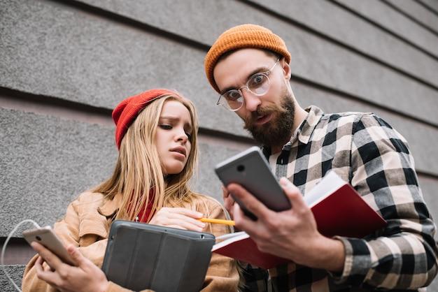 Drukke studenten die studeren, zich voorbereiden op examens, online informatie zoeken, brainstormen, multitasken