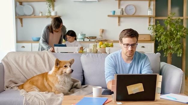 Drukke vader op afstand werken met laptop zittend in de keuken. een schattige kleine hond ligt vlakbij op de bank.