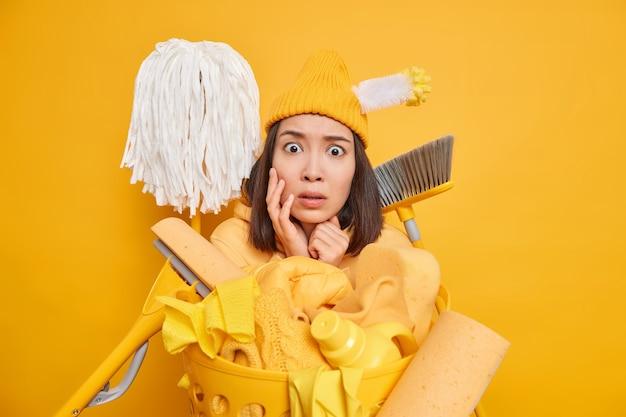 Drukke, verwarde brunette aziatische vrouw kijkt doodsbang naar de camera omringd door schoonmaakspullen en staart bezorgd geïsoleerd over gele muur