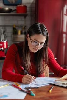 Drukke vrouw denkt aan doelwit of planbedrijf, doet statistieken of analytisch onderzoek, zit aan de desktop, keukeninterieur