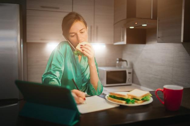 Drukke vrouw eten, koffie drinken, praten aan de telefoon, tegelijkertijd op laptop werken. zakenvrouw meerdere taken uitvoeren