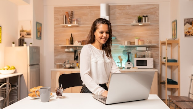 Drukke vrouw in huiskeuken die laptop gebruikt om aan bedrijfsproject voor baan te werken. geconcentreerde ondernemer in huiskeuken met behulp van notebook tijdens de late uurtjes in de avond.