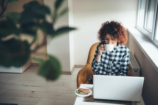 Drukke vrouw met krullend haar en brillen die een thee met broodjes drinken tijdens het werken op de laptop