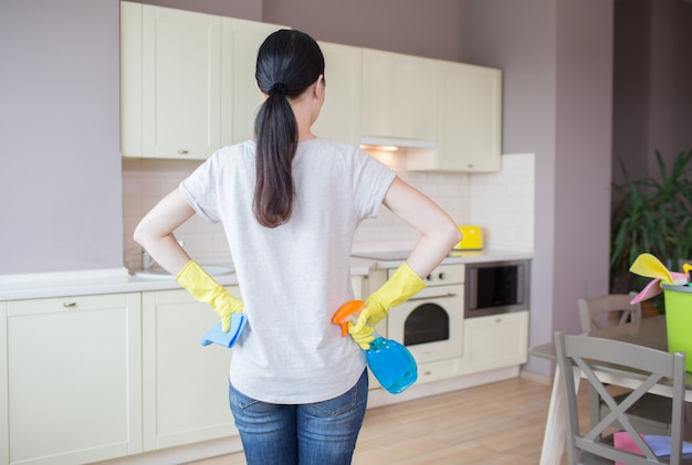 Drukke vrouw staat in de keuken en kijkt naar meubels. ze draagt gele handschoenen. meisje heeft blauwe spray in één hand en doek in een andere. ze is klaar om de kamer schoon te maken.