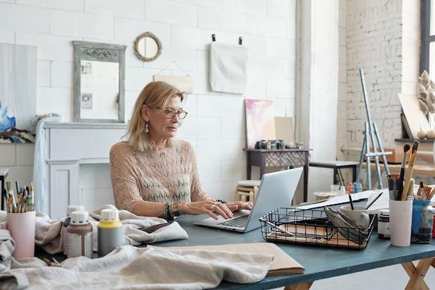Drukke vrouwelijke artiest met blond haar aan tafel zitten en typen op laptop in eigen studio