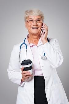 Drukke vrouwelijke arts met smartphone