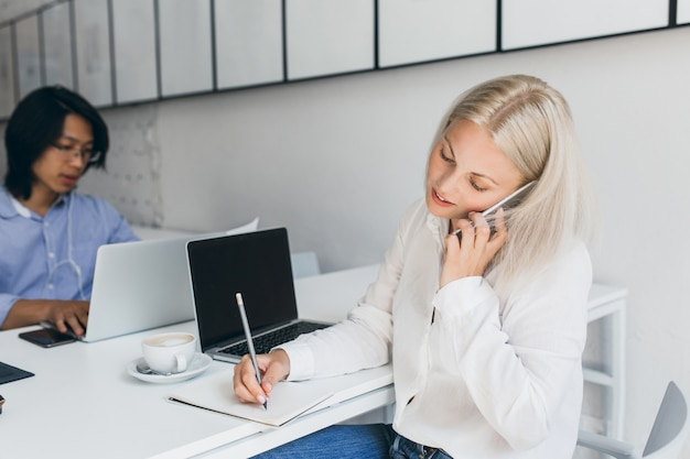 Drukke vrouwelijke blonde student praten over de telefoon en koffie drinkt