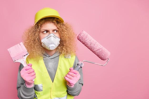 Drukke vrouwelijke decorateur houdt kwast en roller vast die huisrenovatie gaat doen, kijkt aandachtig naar de muur, ze moet poses schilderen in veiligheidskleding tegen roze muur