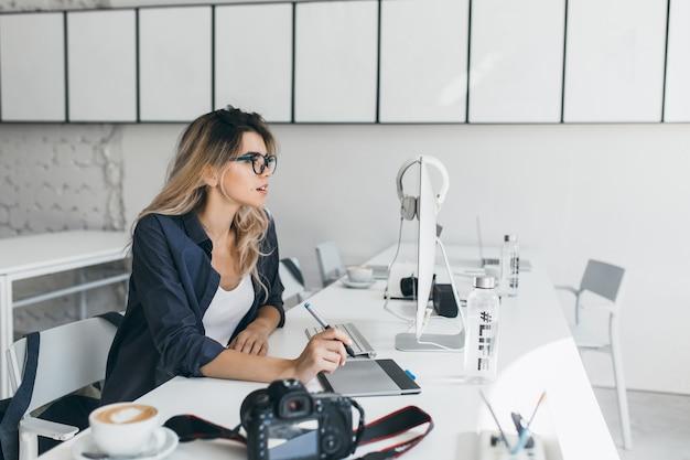 Drukke vrouwelijke europese student die met computer werkt en koffie drinkt
