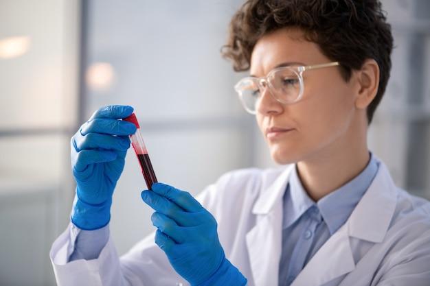 Drukke vrouwelijke laboratoriummedewerker in latexhandschoenen die kleur van bloedmonster van coronaviruspatiënt in reageerbuis analyseren