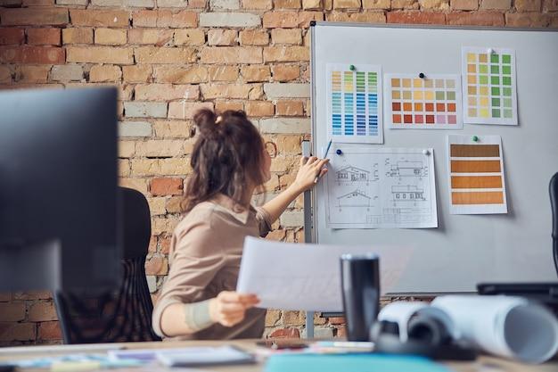 Drukke vrouwelijke ontwerper die blauwdrukpapier en kleurstalen aan boord bevestigt tijdens het werken