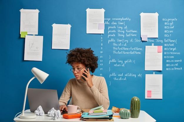 Drukke vrouwelijke secretaris typen tekst op laptopcomputer, stuurt feedback, bladert website, geconcentreerd in scherm, maakt telefoontje.